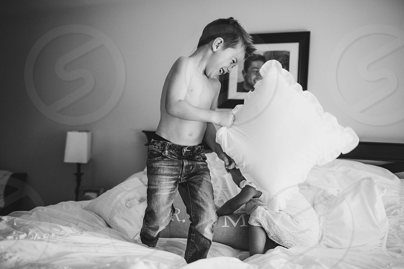 boy wearing denim jeans throw pillow on bed photo