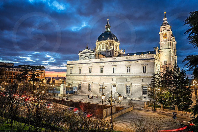 Almudena Cathedral in Madrid at dusk. La Almudena is the Catholic cathedral in Madrid. Interior designed in a Gothic revival style and exterior in baroque to match the nearby Palacio Real. Exterior view against blue sky day. photo