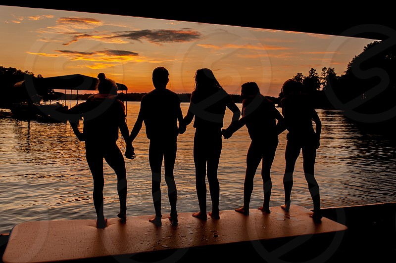 Friendship silhouette sunset lake holding hands photo