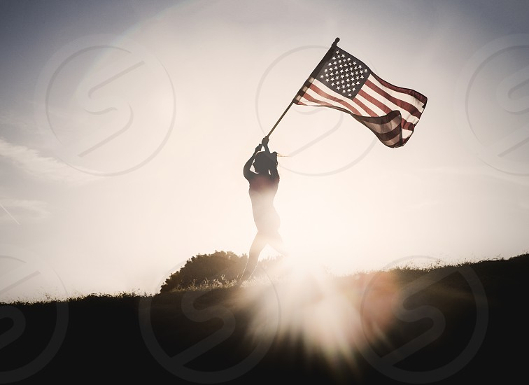 Woman silhouette running while holding a flag.  photo