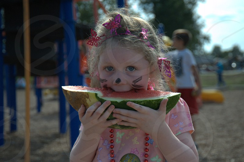 Little girl eats watermelon slice photo