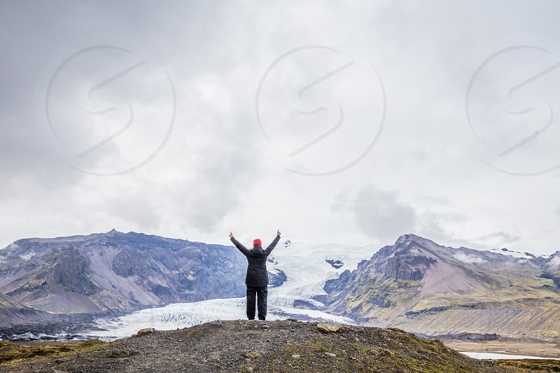 Person with raised arms in front of a glacier in Iceland photo