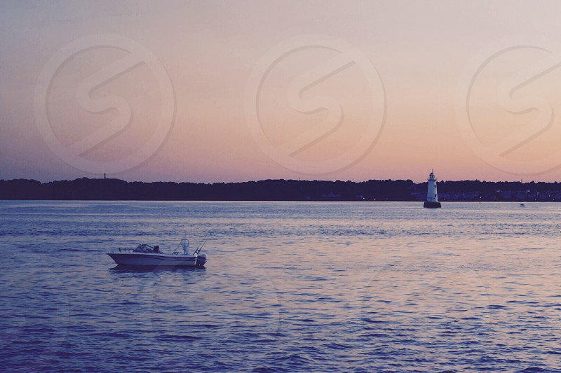white speedboat in body of water during sunset photo