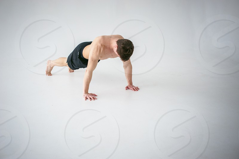 young sexy handsome men of strong Athlete's body with bare torso Dressed black sports shorts portrait of studio of light-skinned strong man engaged in push-ups on floor straining powerful hands photo