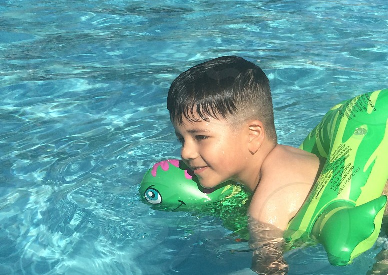boy riding on green turtle inflatable ring photo