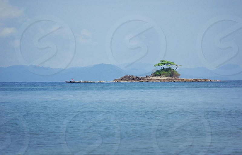 island in the middle of the sea photography photo
