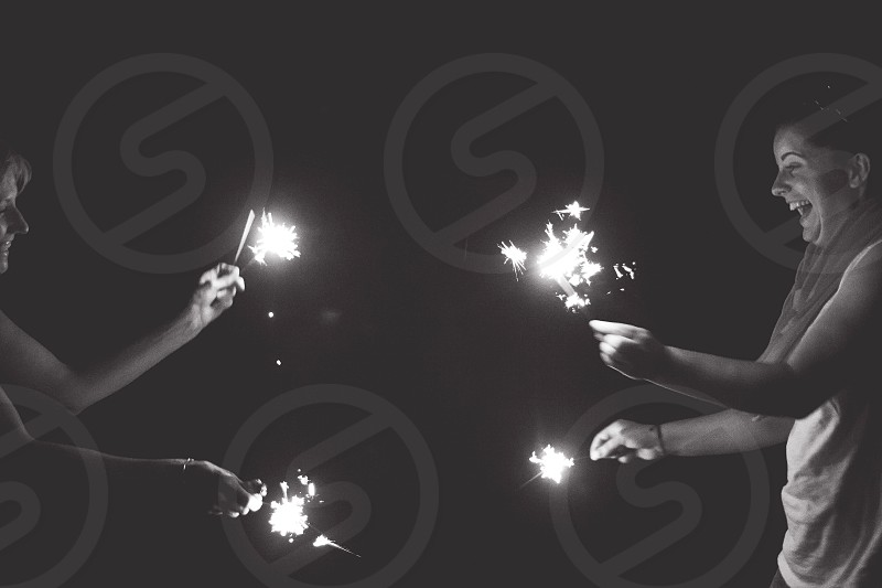 woman playing a sparkler grayscale photography photo