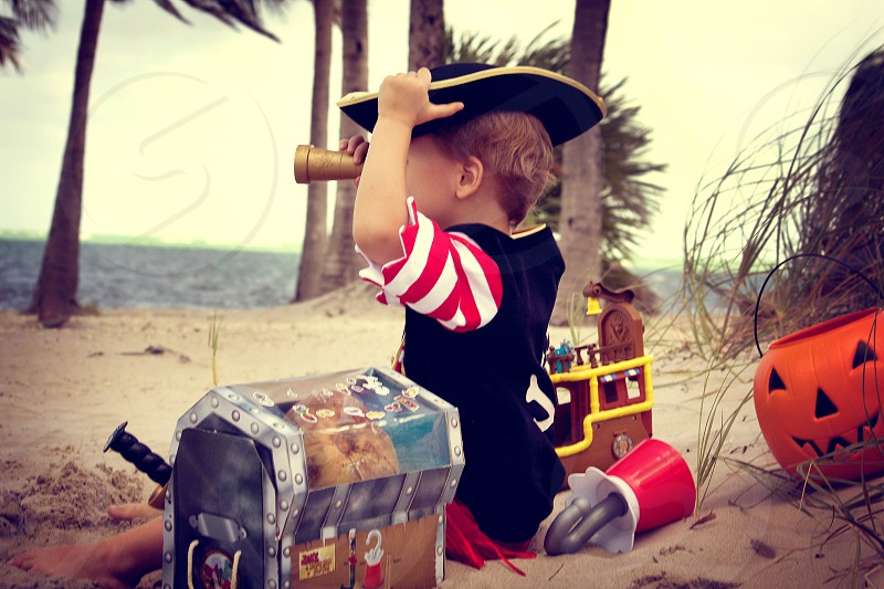 boy in white and red stripe elbow sleeve shirt wearing black hat while using scope and sitting on white sand beside jack o lantern frame photo