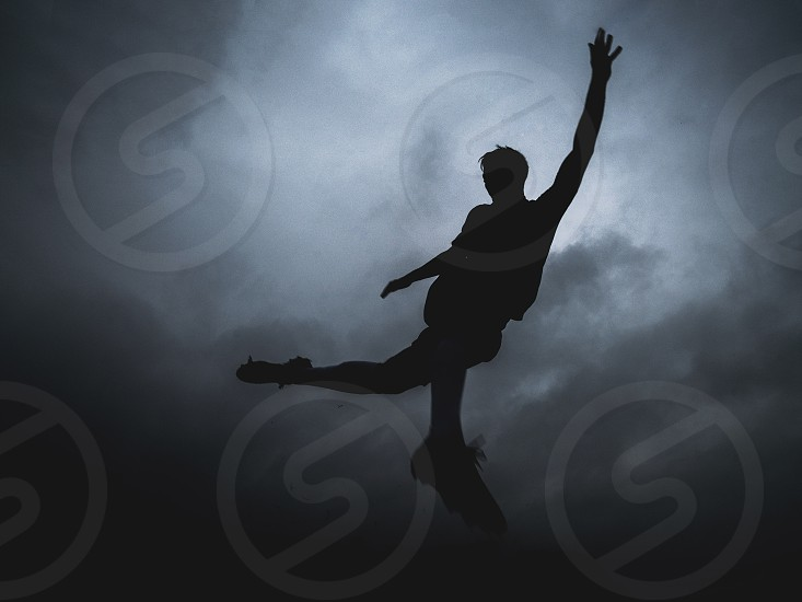 silhouette of man jumping while raising left arm photo