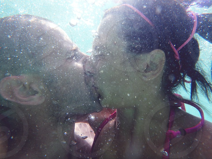 Young couple kissing underwater photo