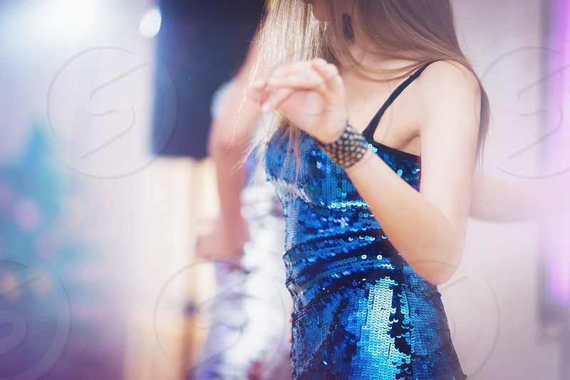 Young woman dancing in bright blue tinsel dress photo