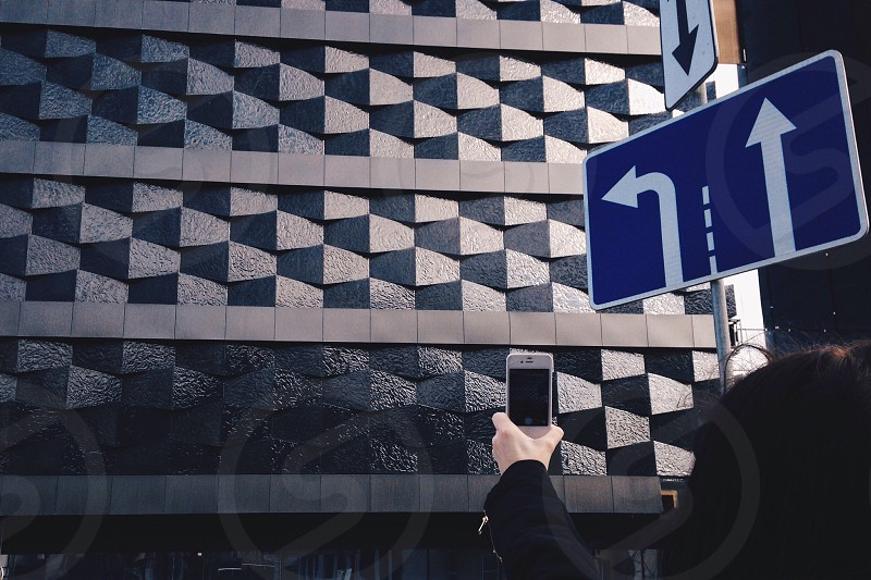 person holding smartphone beside road sign photo