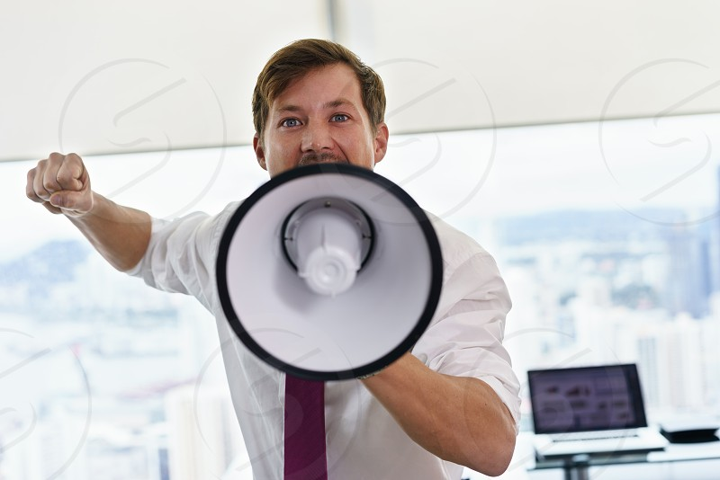 man; businessman; megaphone; screaming; labour; labor; trade union; fight; rights; protest; office; announcement; power; concept; energy; confident; corporate; determination; adult; aggressive; angry; business; business person; career; employee; energetic; executive; fist; freedom; furious; hand; holding; inspiring; job; loud; occupation; one person; people; profession; rage; rebellion; rebel; respect; shouting; syndicate; strength; suit; white collar; worker photo