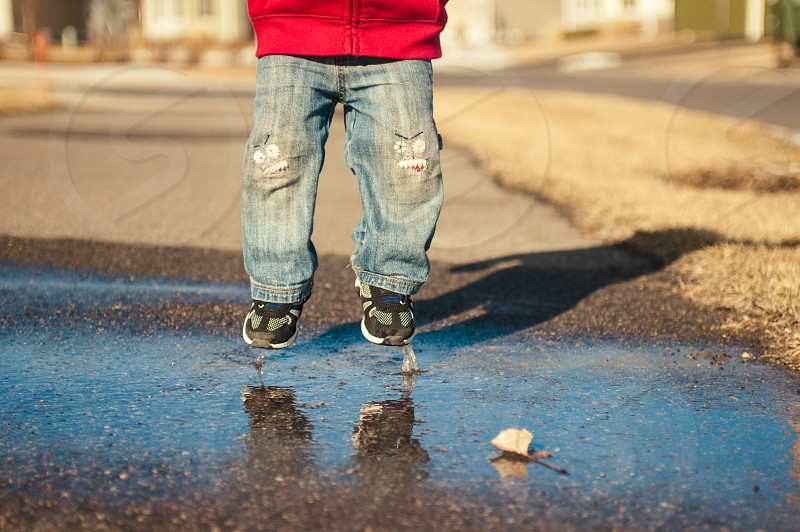 A boy jumping enjoying his youth while jumping in puddles outside in the fall.  photo