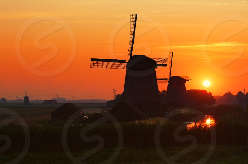 windmills near houses and river during sunset photo