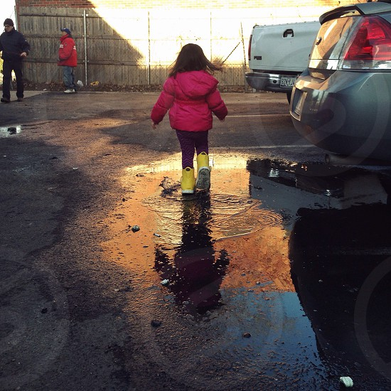 girl in pink jacket and yellow rubber boots in puddle in parking lot photo