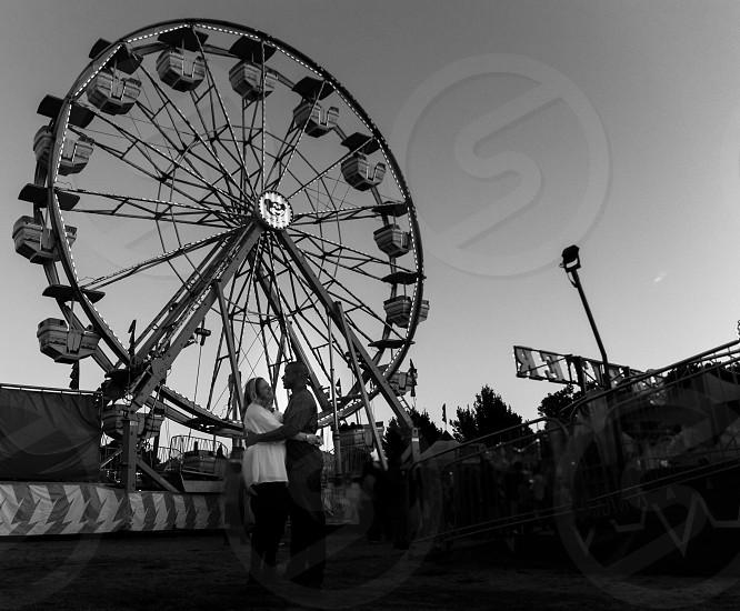 man and woman hugging near the ferris wheel photo