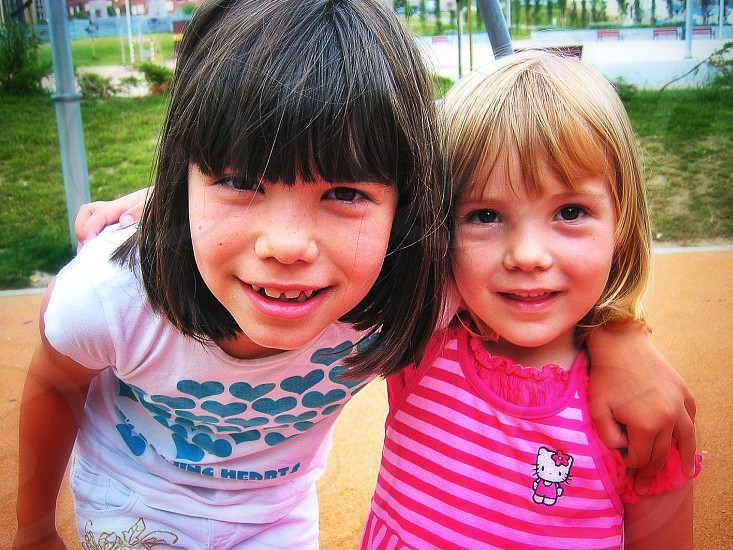 two girls with bangs smiling in park photo