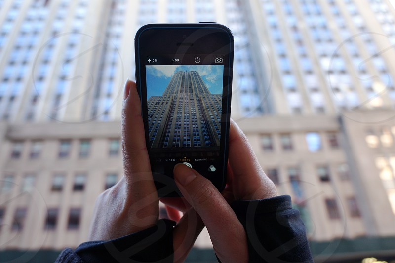 person taking photo of gray concrete high-rise building using iPhone during daytime photo