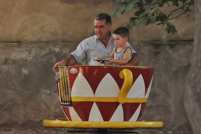 man and boy riding cup and saucer amusement park ride photo