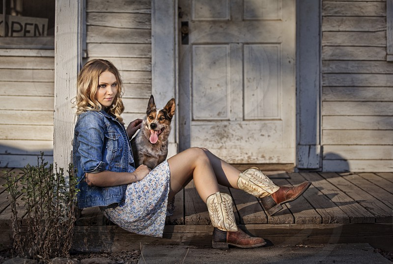 young woman country girl dog heeler dress cowboy bots rural setting rustic dress denim relax rural country porch boots fashion wood photo