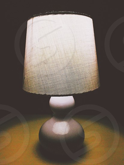 round grey ceramic table lamp with grey fabric lamp shade shining light onto brown wood table with black background photo