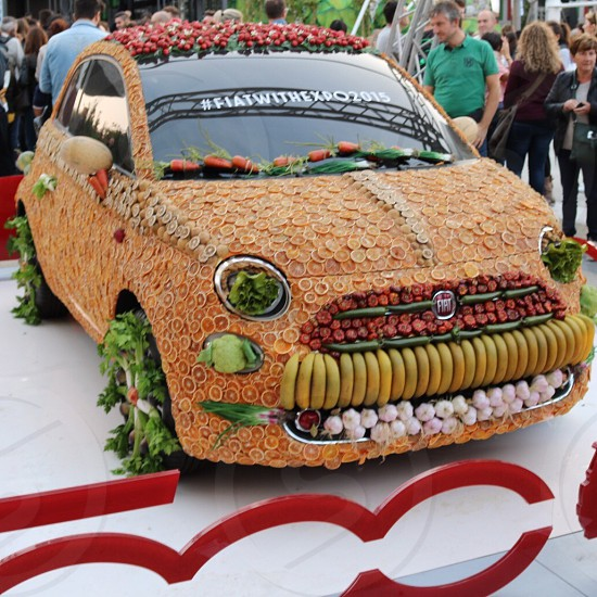 fruits and vegetables covered FIAT 500 surrounded by people during daytime photo