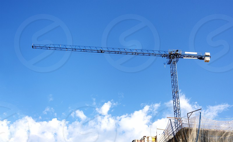 a crane lifting weights on a construction site with a blue sky and clouds on the background. construction and construction engineering. photo