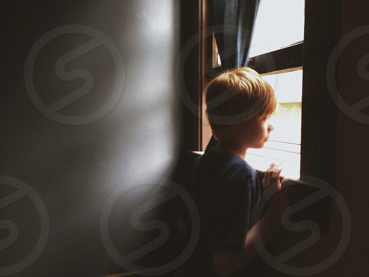 boy looking outside window photo