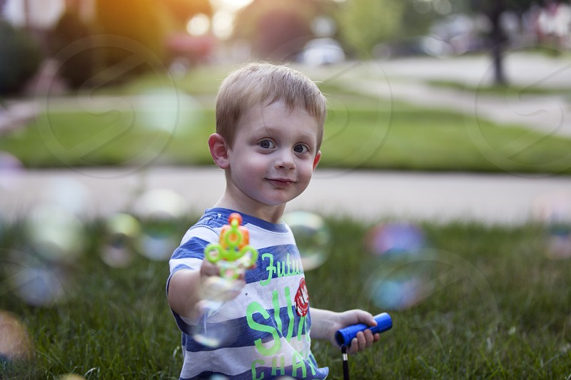boy in white blue stripe shirt playing with bubble maker photo