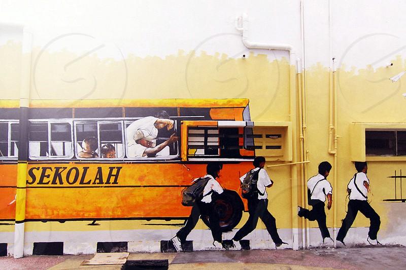 4 boys wearing school uniform beside yellow and black school bus photo