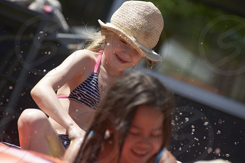 Two girls best friends playing together in a small wading pool in the back garden splashing water photo