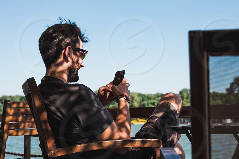 Young man in a cafe by the river using smartphone photo