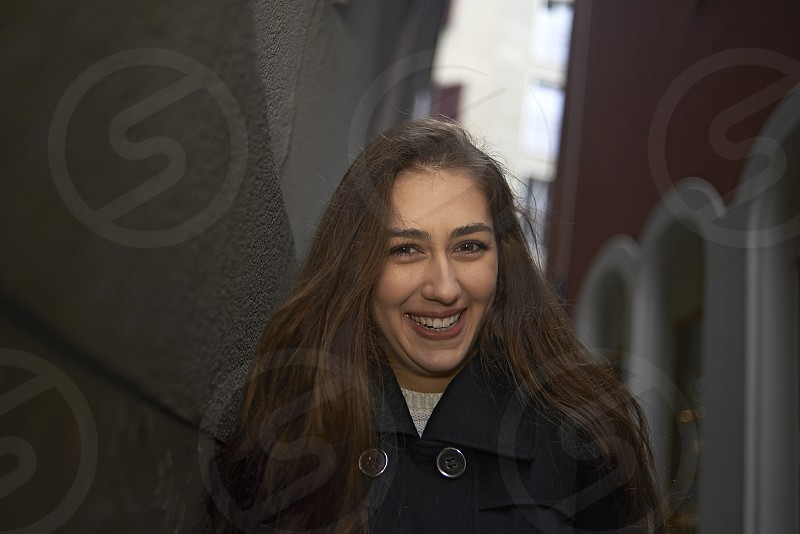 Young wealthy woman walking in an alley and smiling into camera photo