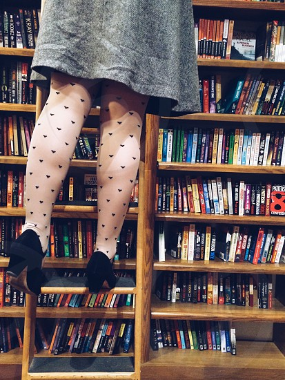 woman wearing gray dress and black chunky heeled shoes step brown wooden ladder in front of brown wooden book shelf photo