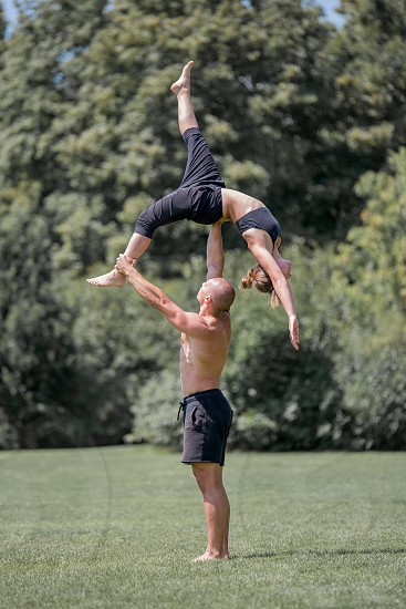 Acro yoga two sporty people practice workout in pair couple doing stretching exercise in the nature. photo