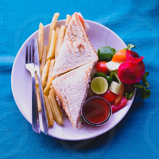 Sandwich with French Fries and fresh salad on blue table cloth photo