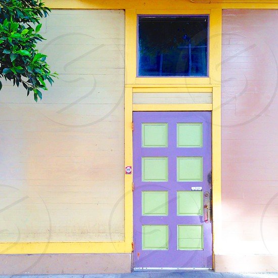 purple and green painted wooden door with grey bricked walls photo