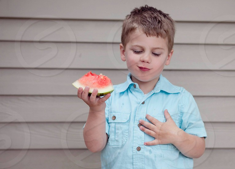 boy in blue button up shirt holding sliced watermelon photo