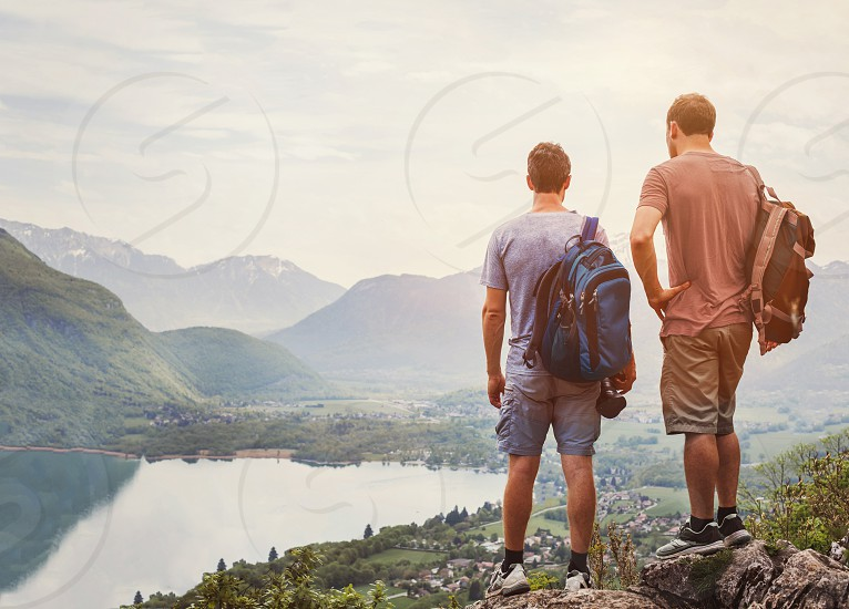 friends hiking in Europe hike in Alps in Annecy France outdoor summer activity with backpack two people backpackers standing on top of mountain and enjoying beautiful nature landscape background photo