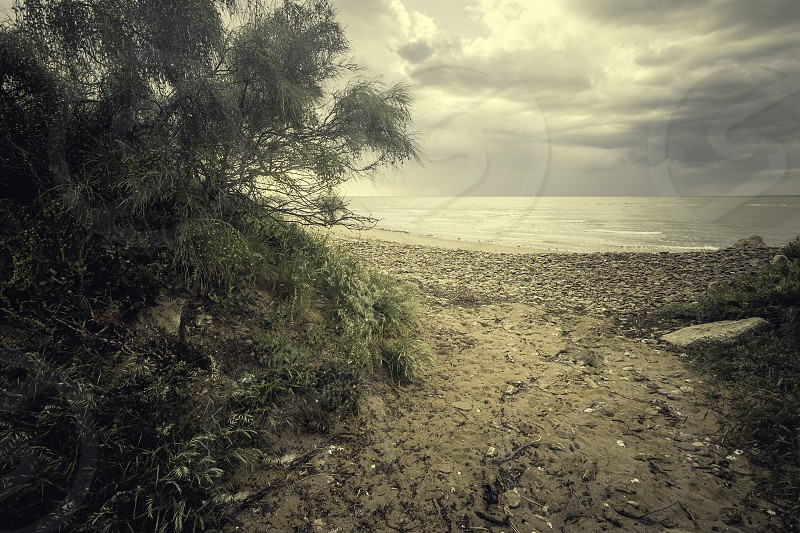 Access to the beach of Sanlucar de Barrameda through a sand road on a day with black clouds photo