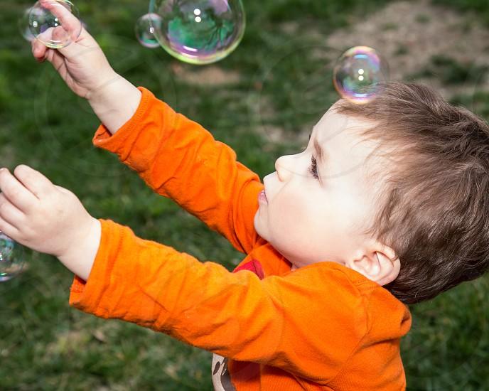 Little toddler boy chasing bubbles photo