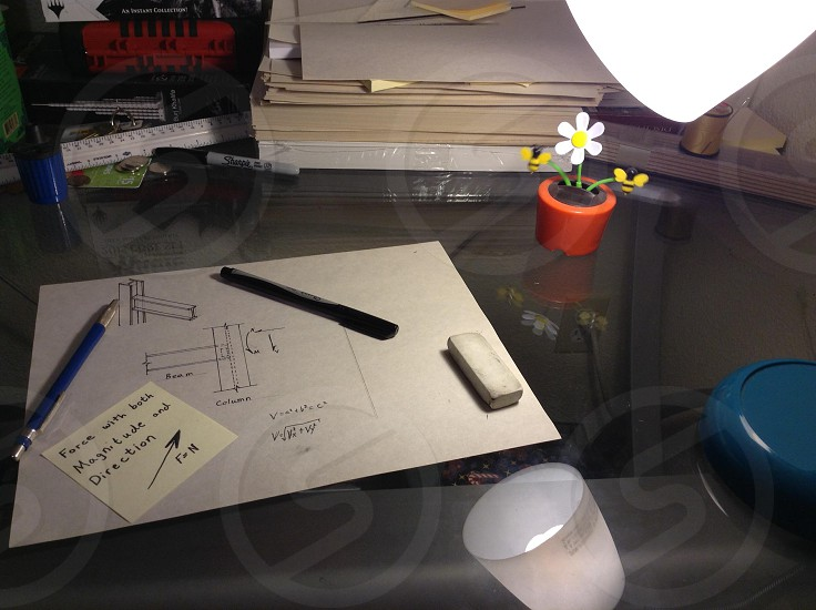 white eraser blue pencil and black pen on white paper with printed diagram on glass-top table photo