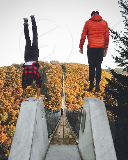 man in red gingham sport shirt and man in red bubble hoodie doing stunts on bridge photo