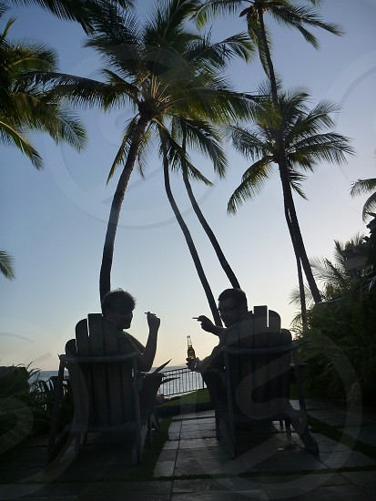 2 men holding cigarettes and beer lying on outdoor bed under coconut palms photo