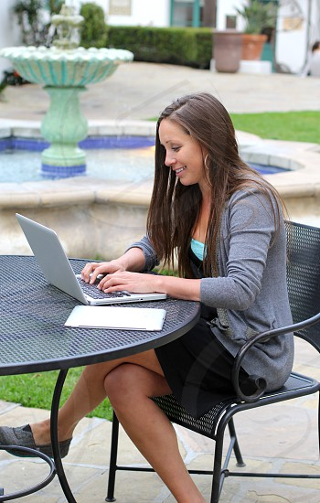 Woman working on laptop in beautiful urban environment. photo