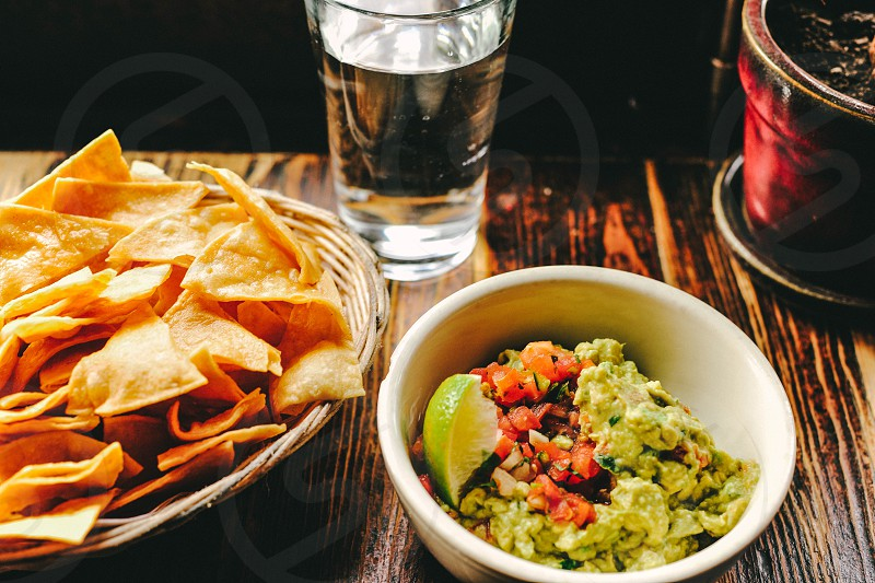 pico de gallo and guacamole in a bowl next to a basket of tortilla chips and glass of water photo