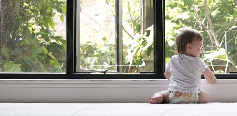 baby in white shirt wearing diaper sitting on white floor infront of window during daytime photo