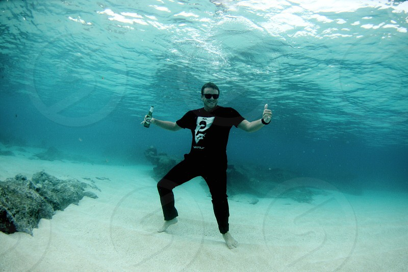 man in black shirt under water smiling photo