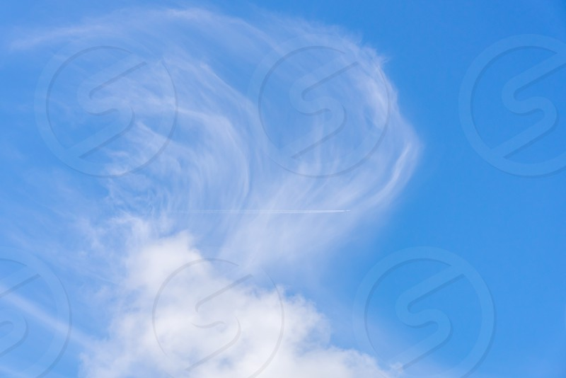 A jets stream and clouds in a blue sky. photo